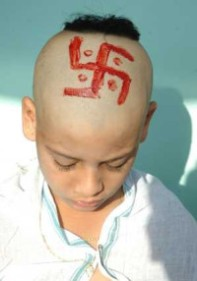 Hindu boy with a swastika drawn on his head during a upanayana ceremony