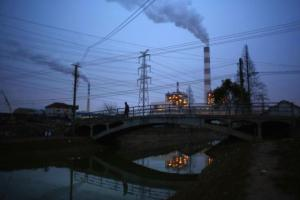 A man walks over a bridge as smoke rises from chimneys of a thermal power plant in Shanghai